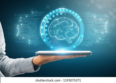 Close up and side view of hand holding tablet with digital brain interface. Ai and technology concept