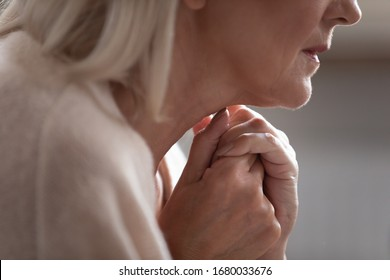 Close up side view older worrying retired woman joined hands together, thinking of personal or health problems. Unhappy middle aged woman suffering from mental disorder, dementia or loneliness.