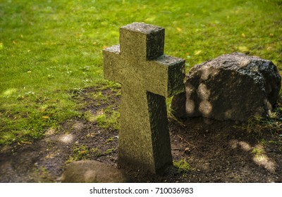 Close up side view of one alone stone cross signs in a meadow area, on green grass background.