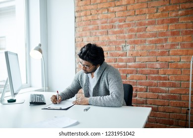 close up side view photo. freelancer writing something in the loft room. man writing a report