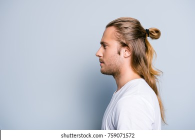 Close up side view photo of serious confident young guy, he has hair bun, isolated on grey background