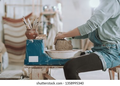 Close up side view picture of craftswoman sitting on bench and creating clay pot on pottery wheel