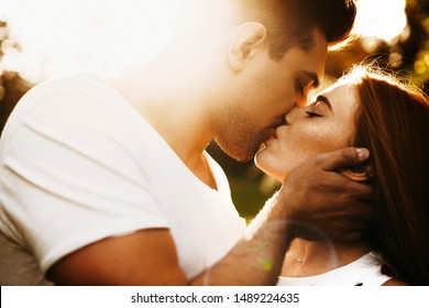 Close up side view portrait of a beautiful woman with red hair and freckles kissing with her boyfriend with eyes closed while against sunset.