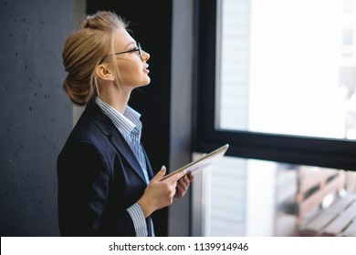 close up side view portrait of pleasant woman with fair hair holding her laptop and looking at the panorama window