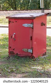 A Close up side view of a red old rusted post offcie post box storage unit