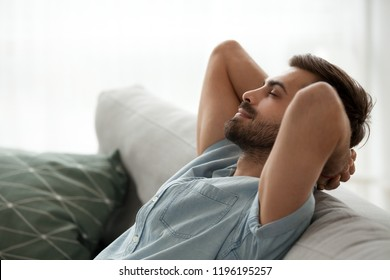 Close up side view serene man smiling sitting on couch at home. Male has a break after work or study closing eyes putting hands behind head relaxing thinking, feels happy breathing fresh air concept