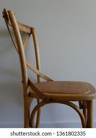 Close up of the side view of a simplistic but trendy wooden dining chair with a woven seat and decorative curves isolated against a white background in Australia