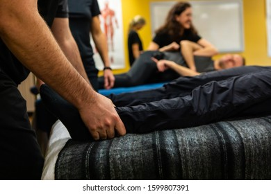 A close up and side view of a Swedish massage student training on the legs of a man, practicing the different bodywork skills, with blurry background