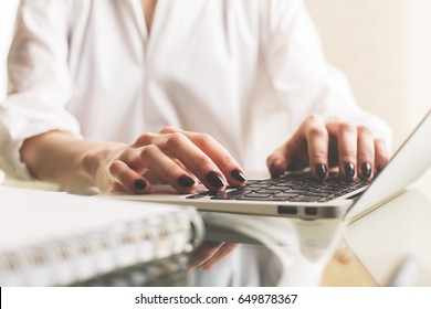 Close up and side view of woman's hands typing on laptop keyboard