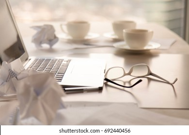 Close up side view of work desk with laptop, coffee, glasses and crumpled paper on table, search for new ideas concept, mess at workplace after meeting, creativity crisis, hard work with no solution