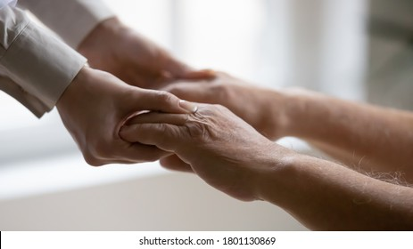 Close up side view young female doctor nurse holding wrinkled hands of elderly mature patient, helping standing up. Old 80s man involved in rehabilitation process with professional therapist indoors.