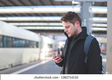 Close up side of young German man with smartphone at train station. People using application on mobile phone. Business travel