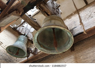 A close sight of two big ancient bells with their clappers and yokes, seen from below, in the belltower of Mary Magdalene church (Iglesia de la Madalena) in Tarazona, Aragon, Spain
