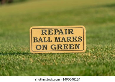 Close up of a sign at a golf course reading Repair Ball Marks On Green