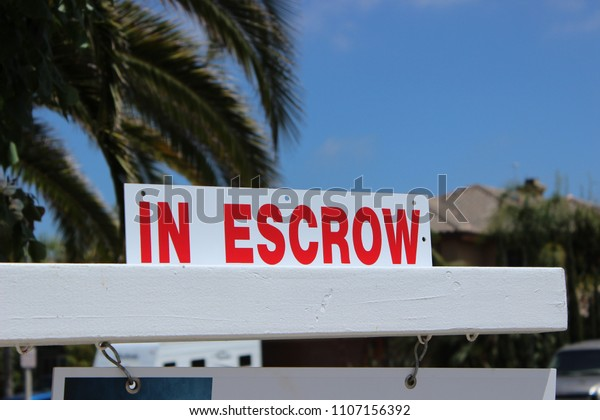 """Close up of a sign """"in Escrow"""" on a home sold in San Diego County, California"""