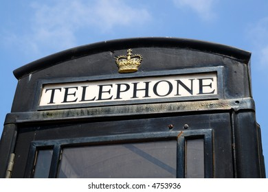 Close up of the sign on a black British telephone box in Cornwall.