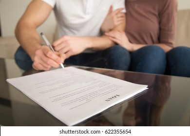 Close up of signing loan agreement, couple sitting on sofa, male hand with a pen setting signature, taking bank credit with easy terms of payment and low interest rate for purchasing property
