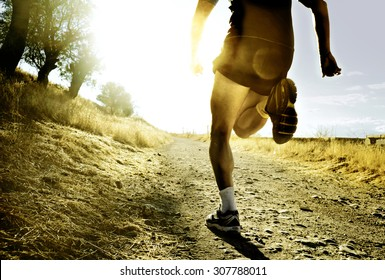 close up silhouette legs and feet of extreme cross country man running and training on rural track jogging at sunset with harsh sunlight and lens flare in countryside sport and healthy lifestyle