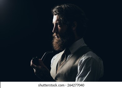 Close up Silhouette Man with Long Goatee Beard Holding a Smoking Pipe While Looking to the Left of the Frame on a Black Background.