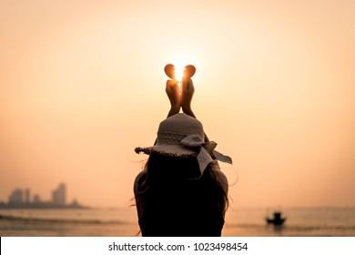 Close up and Silhouette of Woman hand holding broken paper red heart on sunset. Love, Wedding and Valentines day concept.