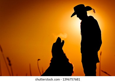 Close up silhouette of a young cowboy and his loyal ranch dog out in the countryside at sunset.