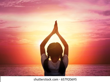 Close up Silhouette of A young girl practicing Yoga vrikshasana tree pose on tropical beach with sunset sky background, watching the sunset, background and copy space. Yoga for kids concept.
