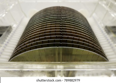Close up of Silicon wafers prepared for production  in a semiconductors manufacturing facility, blurred background