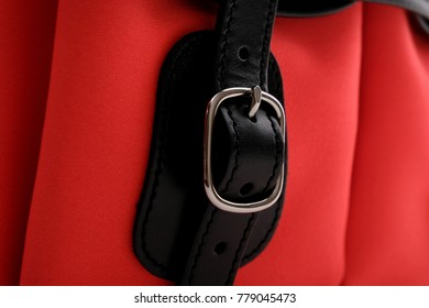 Close up of silver buckle on neon red and black leather trim colour bag