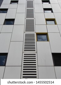 close up of silver colored metal cladding panels on a modern building with repeating windows and geometric grid design