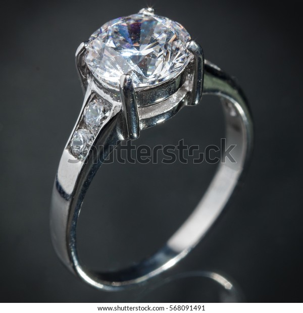 close up silver diamond ring on gray background, vignette effect