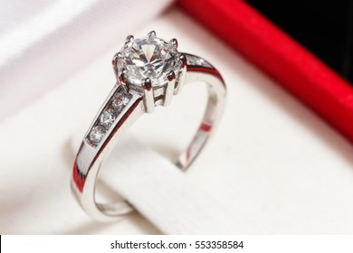 close up silver diamond ring in red ring box