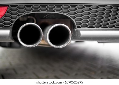 Close up of a silver exhaust pipe of a back car. The grille is made of a black honeycomb pattern. Close up. Selective focus.
