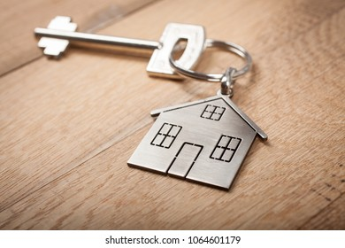 Close up silver home shaped keychain with key on wooden background. Mortgage, investment, real estate, property and new home concept