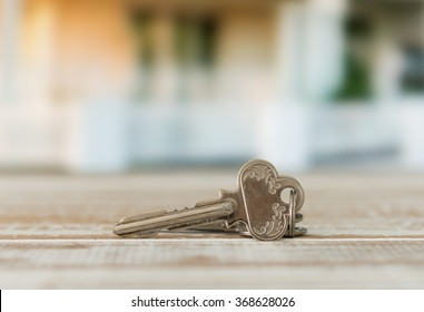 close up silver keys with new house in background.