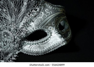 A close up of a silver masquerade mask on black background