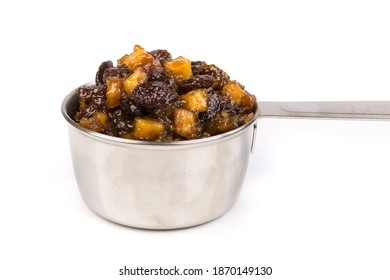 Close up silver measuring cup containing fruit mincemeat mix