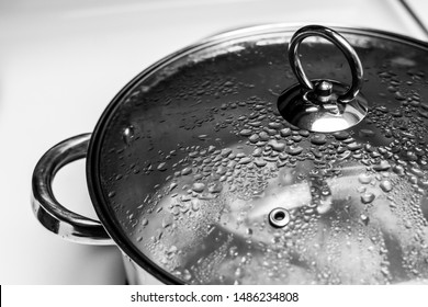 close up of a silver metal pot with lid on circular handle on top with condensation boiling water isolated on white background