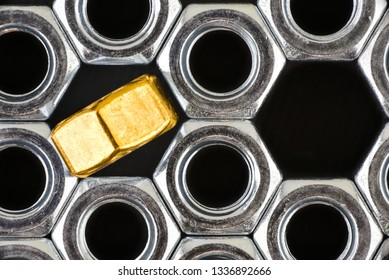Close up silver and one gold hex nuts on black background. Macro photo.