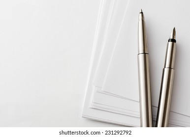 Close up Silver Pens and Blank Bond Papers on Top of White Table with Copy Space on the Left Side.