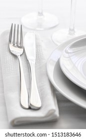 Close up of silverware fork and knife with napkin on white porcelaine plate. Copy space. Restaurant dinning concept.