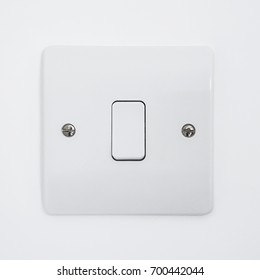 Close up of a simple UK white plastic light switch with a single button affixed to a plain white wall.