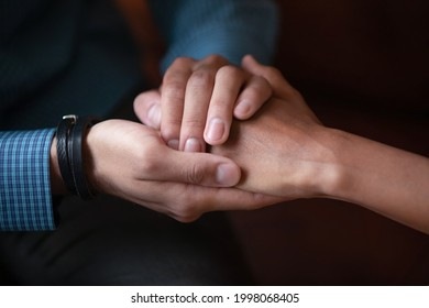Close up sincere empathic young african ethnicity man covering hand of biracial woman, supporting in difficult life situation, giving psychological help, asking forgiveness or making peace indoors.