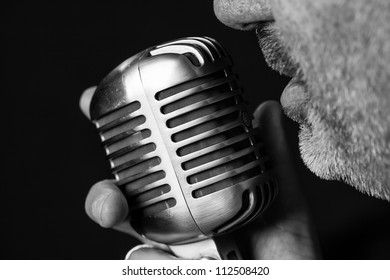 Close up of a singers mouth singing into a vintage microphone with a black background