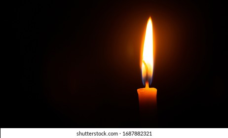Close up single candle light and flame on black background