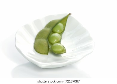 A Close Up of a Single Edamame Soybean Pod, Open to Expose the Soybeans Inside, Sitting on a Beautiful, White Plate