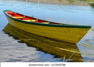 A close up of a single long yellow wooden dory with a red interior and green trim floating in blue still water. The row boat's reflections can be seen in the river along with strands of yellow grass.