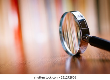Close up Single Magnifying Glass with Black Handle, Leaning on the Wooden Table at the Office. - Shutterstock ID 231292906