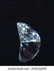Close up single round cut diamond lies sideways on reflective surface against a black background.