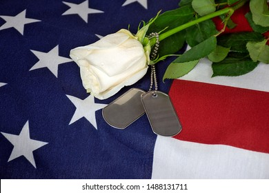 close up of single white rose and military dog tags on American flag