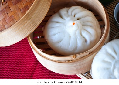 Close up Siopao in bamboo container on red table mat on background